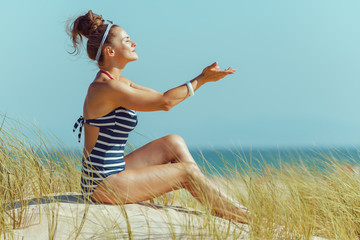 relaxed woman sitting with hands stretched forward on seacoast
