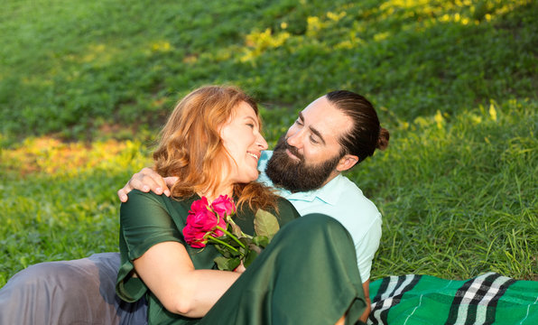 Romantic date. Happy middle-aged couple leisure together on the green grass background.