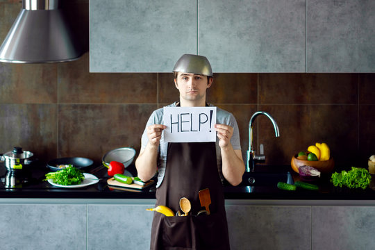 Funny loser man male guy with metal sieve, frying pan, wooden kitchen utensils and apron trying to cook, failed and need help on grey modern loft kitchen. Unsuccessful bachelor on kitchen concept.