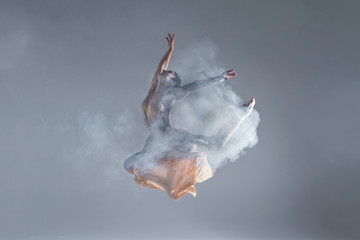Elegant woman female girl ballerina dancer in beige dress dancing, making performance and dance element in fog dust smoke fume on isolated grey background scene. Dancing in cloud concept