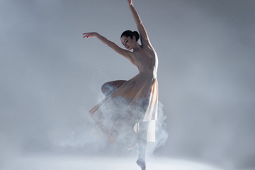 Elegant woman female girl ballerina dancer in beige dress dancing, making performance and dance element ballet in fog dust smoke fume on isolated grey background scene. Dancing in cloud concept