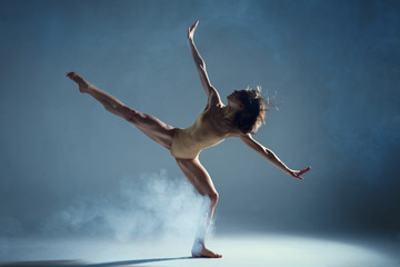 Dancing in cloud concept. Muscle brunette beauty female girl adult woman dancer athlete in fog smoke fume wearing dance bodysuit making stretches dance element performance on isolated grey background Wall mural