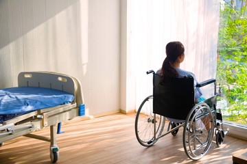 The woman sitting on wheelchair. She is see window with patient bed in hospital. disabled person, lonely. Photo concept depression and Patient.