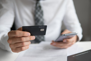 Young businessman with a bank credit card in his hands. Smartphone and Internet Commerce. Payment of goods online. Online trading on the currency exchange. Online payments through the phone.