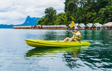 Sport and recreations. Young man enjoy vacations with kayak in Cheow Lan Lake or Rajjaprabha Dam Reservoir, Surat Thani, Thailand.