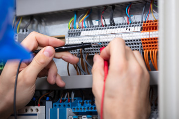 Male Electrician Examining Fuse Box With Multimeter