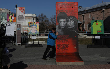 Man poses for a picture next to an art piece painted by artist Jef Aerosol on a section of the Berlin wall in Plovdiv