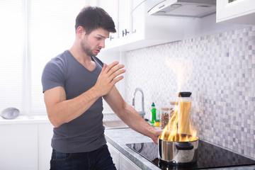Young Man Looking At Burning Cooking Pot