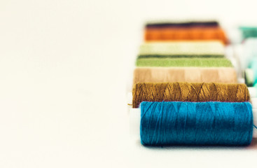 Colored sewing thread coils on white background with copy space for text.