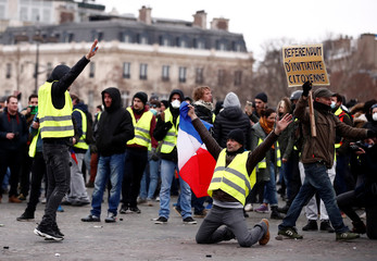 "Protesters wearing yellow vests take part in a demonstration by the ""yellow vests"" movement near the Arc de Triomphe in Paris"