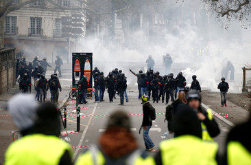 "Police officers are seen in front of protesters wearing yellow vests during a demonstration of the ""yellow vests"" movement in Nantes"