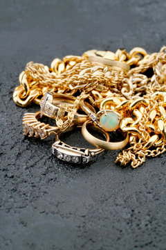 Gold jewelry pile on dark textured background with copy space