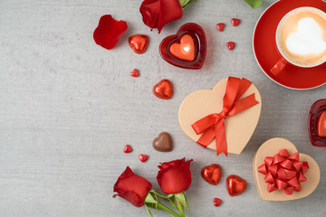 Valentine's day background with coffee cup, heart shape chocolate, candles and gift boxes.