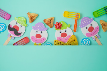 Jewish holiday Purim background with cute paper clowns characters and hamantaschen cookies.