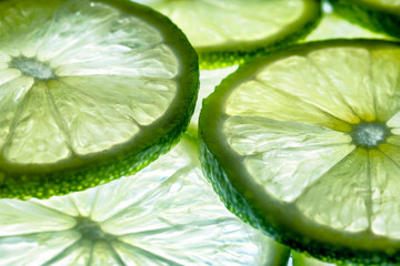 Close up photo of natural glow lime slices in light and shine background