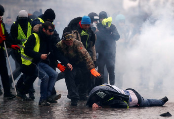 "Protesters wearing yellow vests help a person injured by a water cannon during a demonstration by the ""yellow vests"" movement near the Arc de Triomphe in Paris"