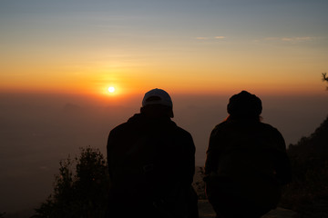 Image of sunrise on orange and yellow horizon with a silhouette of a couple in natural surrounding ( Phu kradueng Thailand )