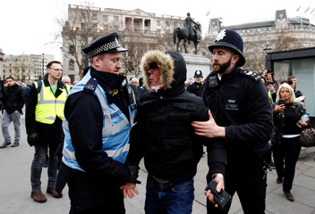 Police officers detain a right-wing supporter during a demonstration march in central London