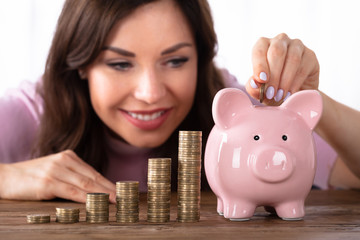 Happy Young Woman Inserting Coin In Piggybank