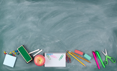 Back to school concept with erased green chalkboard and student supplies