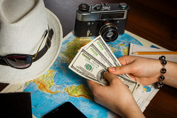 Girl holds dollars on world map background