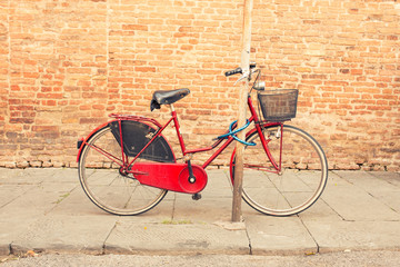 Keuken foto achterwand Fiets Italian red retro bike parked in the old streets of Siena, Italy.