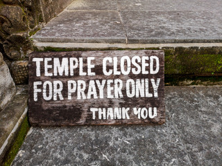 Sign: Temple closed for prayer only. Old wooden board with white letters.