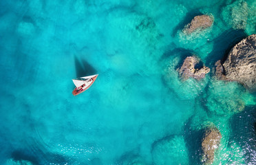 Yacht on the sea from top view. Turquoise water background from top view. Summer seascape from air. Travel concept and idea