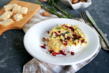 Baked camembert or brie with rosemary, garlic and olive oil. Served with dried cranberries, walnuts and white bread croutons.