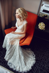 Bride blonde in white wedding dress sitting in a chair in a hotel room. Woman resting before the wedding ceremony. Tired bride sitting with a bouquet of flowers