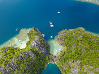 Aerial view to tropical lagoon with azure water and traditional sailing boat near Barracuda Lake, Coron island. Palawan, Philippines.