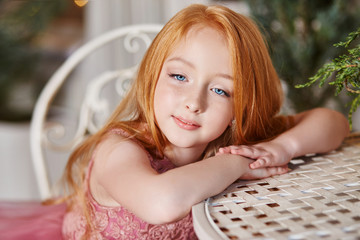 Girl with long red hair in a pink dress sitting at the table. Carnival holiday birthday. Portrait of a cheerful red-haired girl with big blue eyes