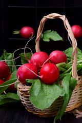 Fresh radish with tops in a wicker basket