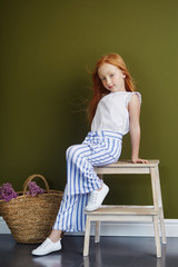 Little red-haired girl with a basket of flowers posing on an olive background. Spring portrait of a redhead girl with blue eyes. Hair the color of fire, Norwegian teen girl