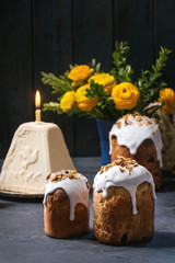 Set of traditional Russian and Ukrainian Easter cake Kulich Paska bread glazed with almond, whole and sliced, with yellow flowers, colored eggs, cottage paskha over dark texture table. Rustic style