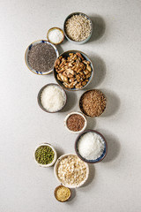 Variety of raw uncooked grains superfood cereal chia, linen, sesame, mung bean, walnuts, tapioca, wheat, buckwheat, oatmeal, coconut, rice in ceramic bowls grey spotted background. Flat lay space