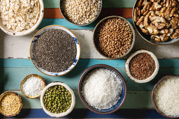 Variety of raw uncooked grains superfood cereal chia seeds, sesame, mung bean, walnuts, tapioca, wheat, buckwheat, oatmeal, coconut, rice in ceramic bowls. Wooden plank background. Flat lay
