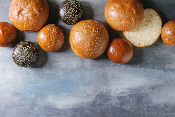 Variety of homemade traditional and black cuttlefish ink different size burger buns with sesame seeds whole and sliced over blue texture background. Flat lay, copy space