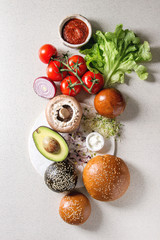 Ingredients for cooking homemade vegan hamburgers. Cheese, avocado, portobello mushroom, tomato, green sprouts, black and white buns, salad, onion. Grey background. Top view, space.