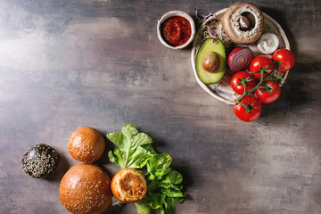 Ingredients for cooking homemade vegan hamburgers. Cheese, avocado, portobello mushroom, tomato, green sprouts, black and white buns, salad, onion. Dark background. Top view, space.