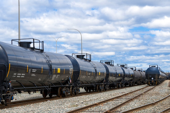 Black railway tanker cars of the type used to transport petroleum products. Several cars visible on two separate sets of tracks. Identification markings have been removed, only technical info remains.