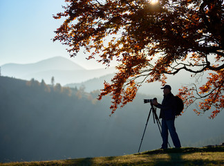 Male tourist photographer with backpack, tripod and professional camera standing under big tree with golden leaves on foggy mountains landscape and sunset in blue sky background.