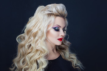 Portrait of a young luxurious blonde with long curls.