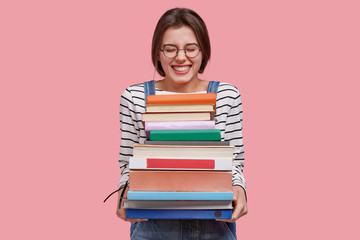 Photo of pleased teenage girl holds heap of textbooks, being in high spirit, wears denim overalls, poses against pink background, likes studying, laughs at something positive. Studying concept