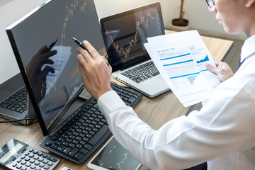 Stock exchange market concept, stock broker looking at graph working and analyzing with display screen, pointing on the data presented and deal on a exchange, Businessman trading stocks online