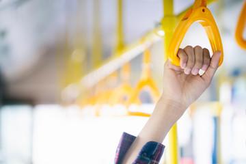 Closeup passenger  hand holding handle on the public transportation.