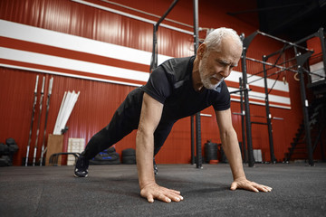 Healthcare, age, retirement and rehabilitation concept. Muscular fit seventy year old unshaven man...
