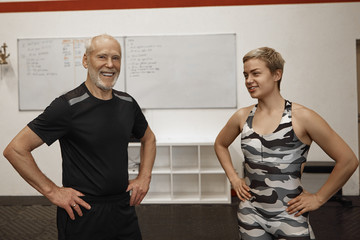 Picture of happy attractive blonde female fitness coach and her bearded senior male client standing next to each other in modern gym interior, smiling or laughing, ready for crossfit training