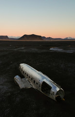 Aerial of a crashed old airplane on a black sand beach in southern Iceland during sunset.