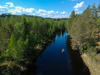 People on a canoe paddling a river in a forest.